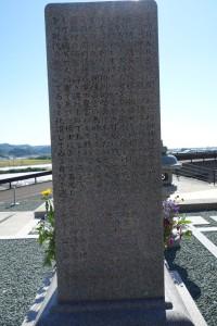 墓石の背面。向かって左側面の文章の続きが彫り込まれている。